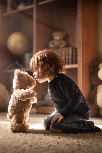 亲吻玩具小熊的小男孩儿童摄影图片