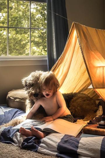 与宠物狗一起看书的小男孩儿童摄影图片