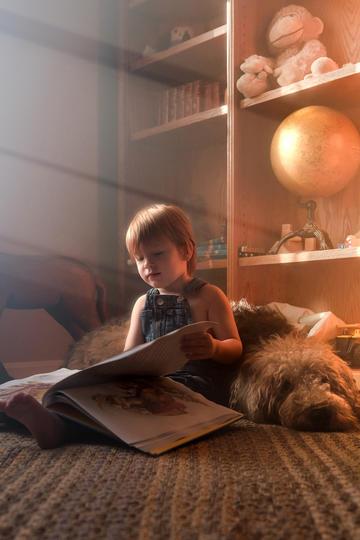 躺在小狗身上阅读的小男孩