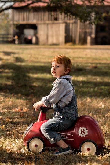 草地上骑玩具车的小男孩儿童摄影图片