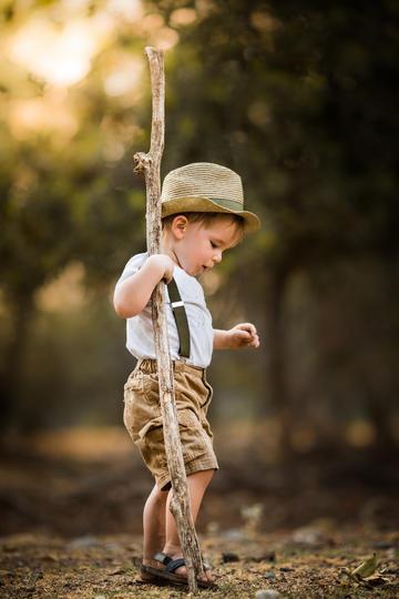 拿着树枝的小男孩儿童摄图