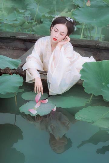 坐在小船上摆弄花瓣的古装美女人像摄影