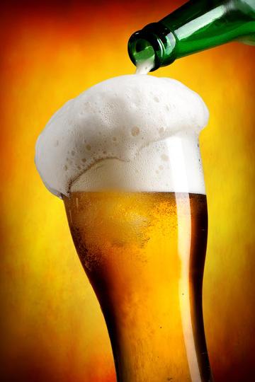 倒满啤酒的杯子商业摄影图片