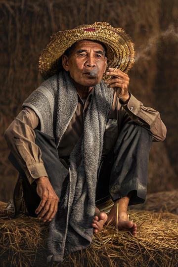 在稻草上抽烟的老人