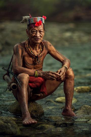 坐在小溪边的少数民族老人