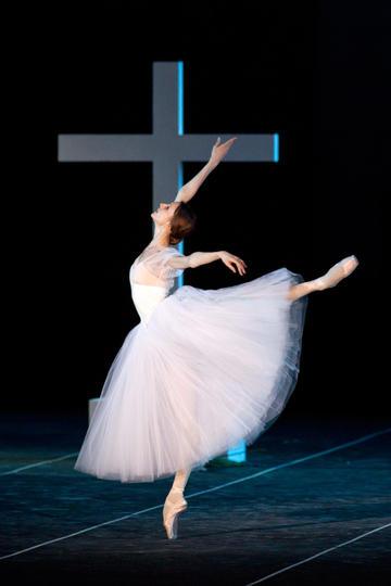 十字架旁跳芭蕾舞的女生