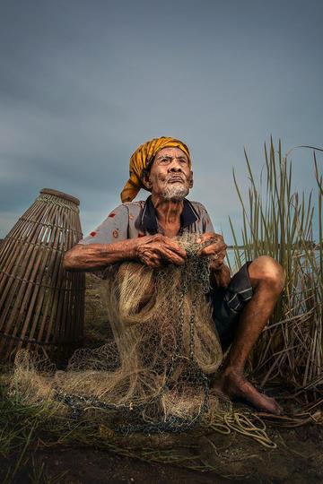 整理渔网的老人纪实摄影图片