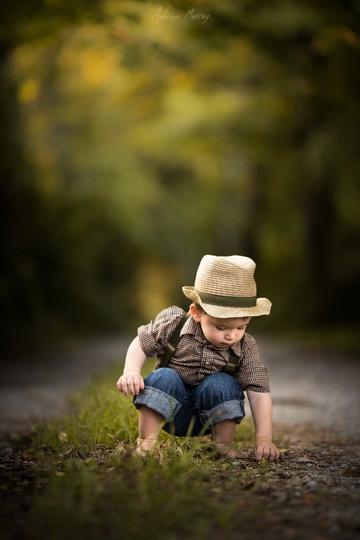 蹲在地上捡石头的小男孩