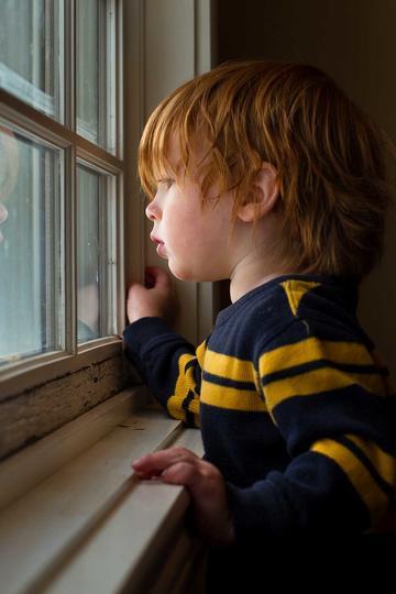 窗户边看风景的小男孩儿童摄影图片
