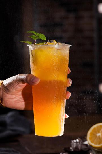 手拿鲜橙汁果汁奶茶图片