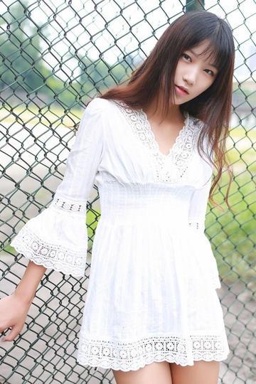 靠在铁丝网上的超短裙美女