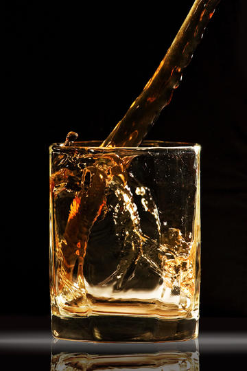 正往杯子里倒威士忌洋酒图片